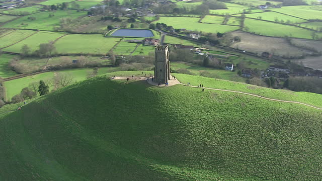 aerial shots glastonbury tor with tourists walking around st michael's tower on a clear sunny day. on in somerset, united kingdom. - glastonbury tor stock videos & royalty-free footage
