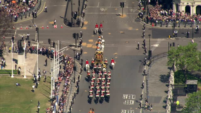 aerial shots houses of parliament with carriage procession departing after state opening of parliament on may 27, 2015 in london, england. - the queen's speech state opening of uk parliament stock videos & royalty-free footage