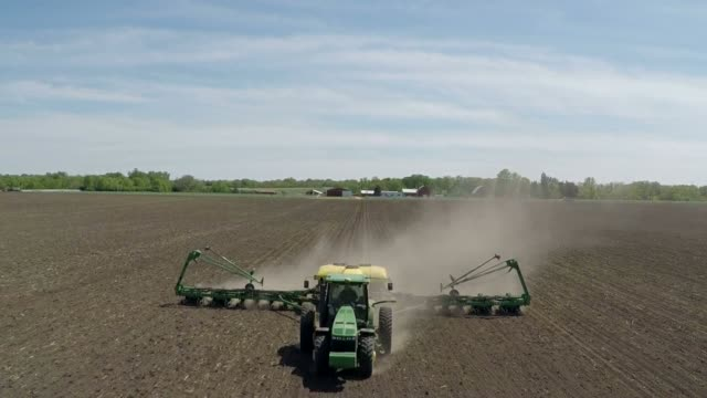 aerial shots look down on a john deere & co tractor pulling a planter as soybeans are planted in a field outside tiskilwa, illinois, us, on... - tractor stock videos & royalty-free footage