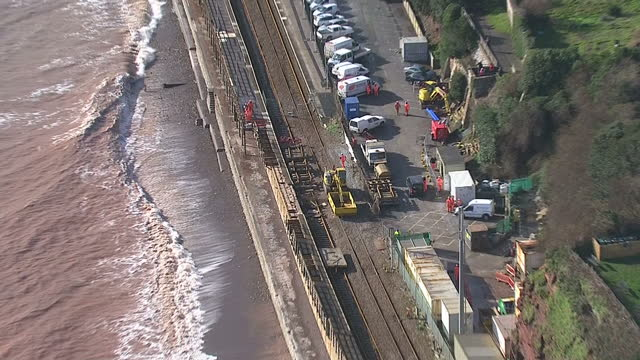 vidéos et rushes de aerial shots network rail working to repair dawlish rail tracks along the sea front with shipping containers placed along sea wall to stop waves... - érodé