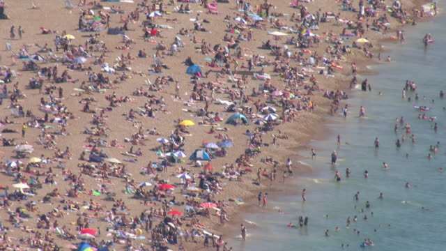 aerial shots of a busy brighton beach with people sunbathing and in the sea during the hottest day in 17 years and people on a jet ski at sea on 7... - summer stock videos & royalty-free footage