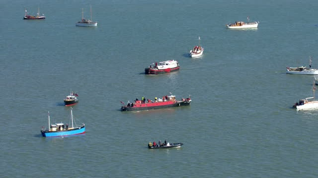 aerial shots of a flotilla of little ships sailing away from the harbour to sea in reenactment of the dunkirk rescue of the second world war on may... - evakuierung von dünkirchen stock-videos und b-roll-filmmaterial
