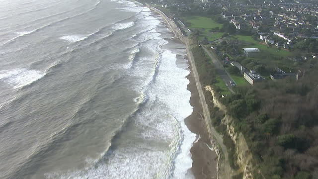 Aerial shots of a high sea level stormy waves crashing along Bournemouth beaches Groynes are visible along the coastline Aerials of Waves Crashing on...