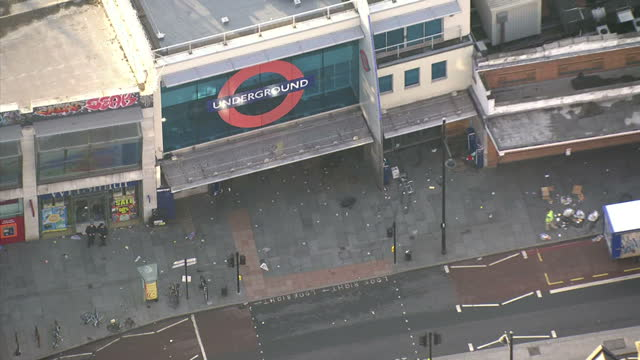 aerial shots of a police van outside brixton underground station after a nights rioting in the area with rubble on streets on august 8 2011 in london... - ブリックストン点の映像素材/bロール