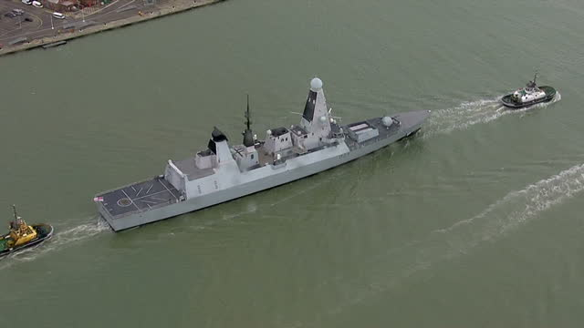 aerial shots of a royal navy type 45 destroyer being escorted past the portsmouth naval shipyards portsmouth dockyard aerials on november 06 2013 in... - 造船所の労働者点の映像素材/bロール
