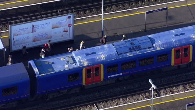 Aerial shots of a South West Trains passenger train travelling along tracks pulling in to a station with passengers embarking and disembarking before...