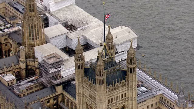 aerial shots of a union jack flag at half mast on the palace of westminster and floral tributes outside the palace of westminster in memory of jo cox... - jo cox politician stock videos and b-roll footage