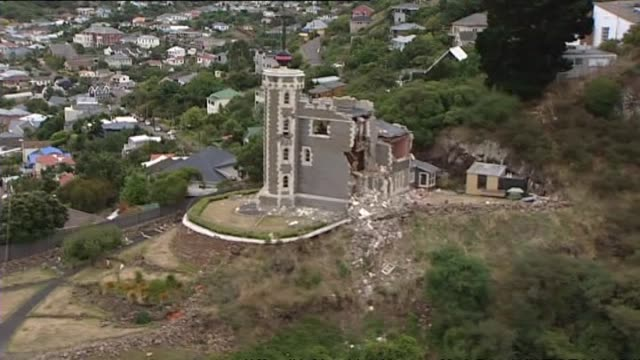 aerial shots of aftermath and damage on city skirts with huge fallen rock at base of cliff stationary petrol tanker truck on sumner road blocked by... - christchurch stock-videos und b-roll-filmmaterial