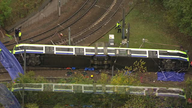 aerial shots of an overturned tram on the tracks and emergency crews on the scene on november 9 2016 in croydon england - train crash stock videos and b-roll footage
