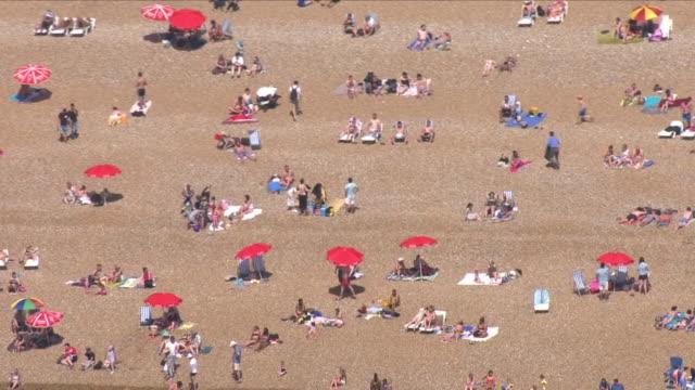 aerial shots of brighton beach and sunbathers on 7 may 2018 in brighton, united kingdom - イーストサセックス点の映像素材/bロール