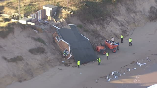 Aerial shots of collapsed houses on top of sand dunes overlooking the sea demolished by an unusually large tidal surge at Hemsby Norfolk with...