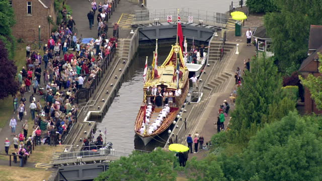 vídeos de stock e filmes b-roll de aerial shots of crowds looking on as the gloriana passes through a lock to join a flotilla celebrating the 800th anniversary of the sealing of the... - magna carta documento histórico