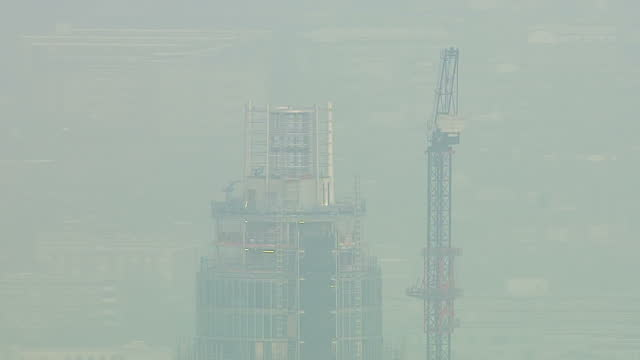 aerial shots of damaged crane where helicopter crashed into with some fog making it less visible two poeple killed in helicopter crash in london on... - ヘリコプター事故点の映像素材/bロール