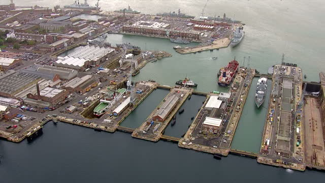 aerial shots of dry docks at portsmouth naval shipyards showing ships in dry docks for maintenance or construction portsmouth dockyard aerials on... - skeppsbyggare bildbanksvideor och videomaterial från bakom kulisserna