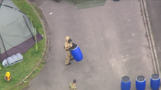 aerial shots of emergency officers wearing protective clothing stood at the scene including shots of military officers wearing protective clothing... - イングランド ケント点の映像素材/bロール