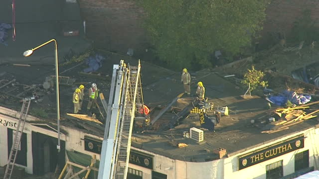 aerial shots of fire and rescue workers at the scene of a helicopter crash in glasgow with a group of workers on the roof of the clutha pub... - ヘリコプター事故点の映像素材/bロール