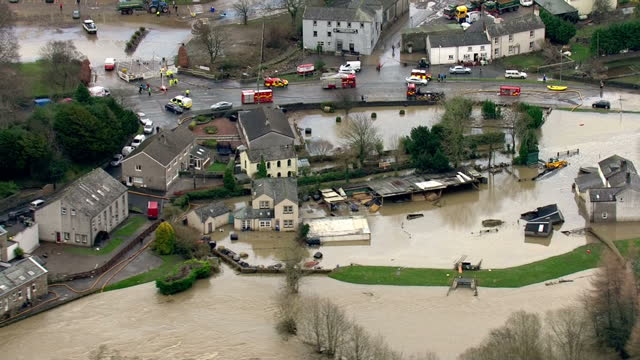 aerial shots of flooding in cockermouth panning along river derwent with burst riverbanks on december 07 2015 in cumbria england - flussufer stock-videos und b-roll-filmmaterial
