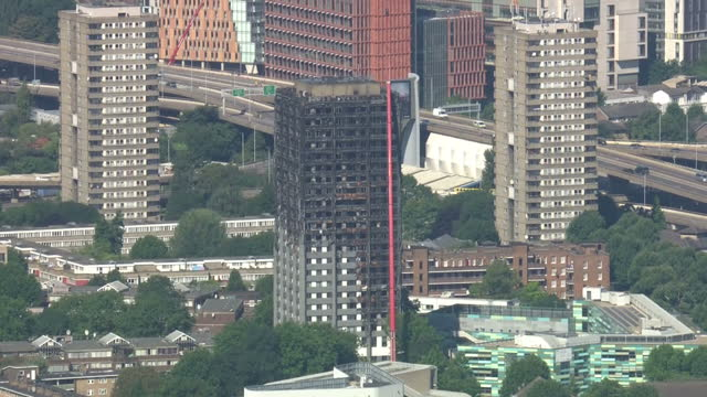 vídeos de stock e filmes b-roll de aerial shots of grenfell towers with the shell of the building burnt out, red crane up against the wreckage of the building, two months on from the... - peckham