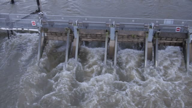 Aerial shots of high levels of fast flowing water on the River Thames at Shepperton and flowing through Shepperton Lock High water on the River...