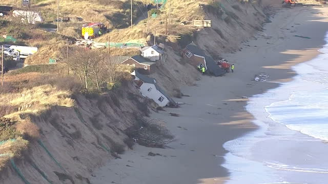aerial shots of houses swept onto the beach at hemsby norfolk by a large tidal surge with authorities on scene helping with salvage operations many... - 2013 stock videos & royalty-free footage