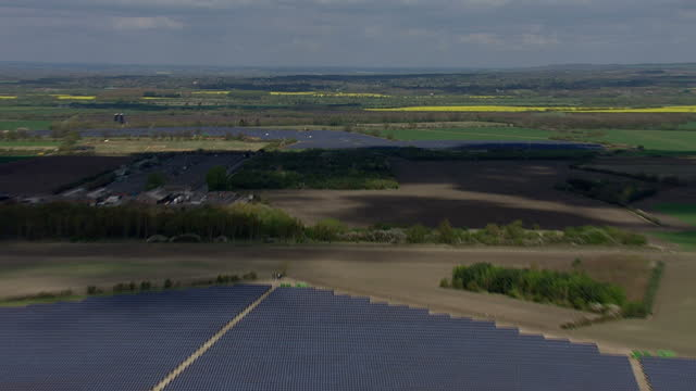 Aerial shots of huge solar panel plantation with energy storage units being installed and diggers prepping land
