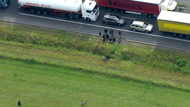 aerial shots of illegal migrants walking across fields and gathered at the side of the road near lorries queueing for the channel tunnel during... - calais stock videos and b-roll footage