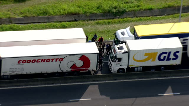 aerial shots of lorries queueing on the road leading to the channel tunnel terminal at calais with shots of illegal migrants attempting to board... - calais stock videos and b-roll footage