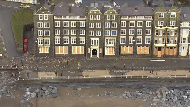 aerial shots of paving slabs and gravel scattered across a seafront road in aberystwyth having been lifted from the promenade by a tidal surge tidal... - aberystwyth stock videos & royalty-free footage