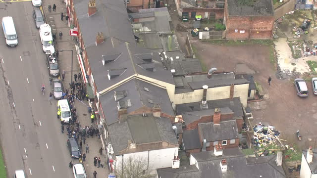 Aerial shots of police and a crowd of media and bystanders outside a flat on Hagley Road Birmingham which was raided by police in connection to the...