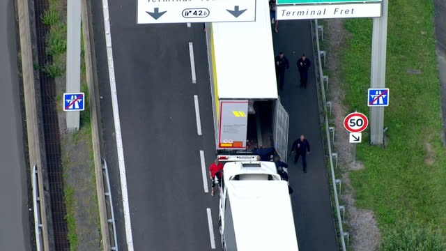 aerial shots of police officers walking alongside lorries queueing for the channel tunnel amid disruption caused by striking ferry workers and... - calais stock videos and b-roll footage