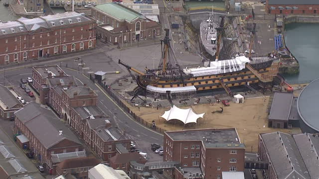 aerial shots of portsmouth historic dockyard including the hms victory partly covered due to restoration works and the naval shipyard with various... - skeppsbyggare bildbanksvideor och videomaterial från bakom kulisserna