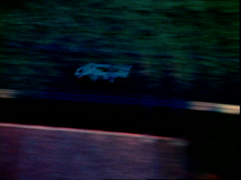 aerial shots of race cars speeding along country roads early morning sprawling forest shrouded in mist / aerial shots of matra simca ms660 ligier js... - 1971 stock-videos und b-roll-filmmaterial