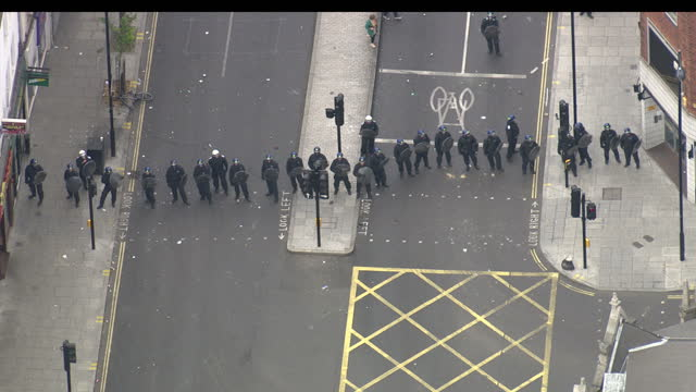 vidéos et rushes de aerial shots of rioters throwing objects at police officers stood in a line formation during the london riots in hackney on august 9, 2011 in london,... - hackney