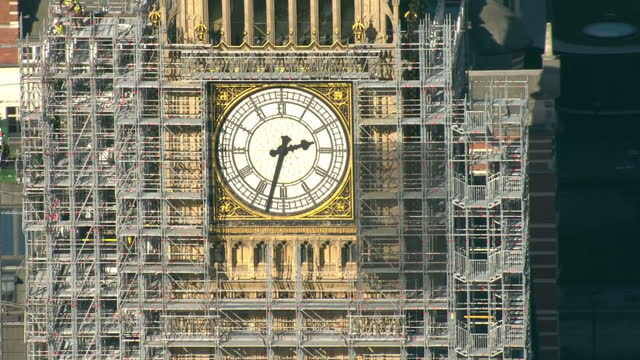 stockvideo's en b-roll-footage met aerial shots of scaffolding surrounding the clock tower of the houses of parliament and construction workers on top of the scaffolding during... - steiger bouwapparatuur