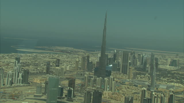 Aerial shots of the Burj Khalifa other sky scrapers in Dubai with the coastline in the background Shot from a plane
