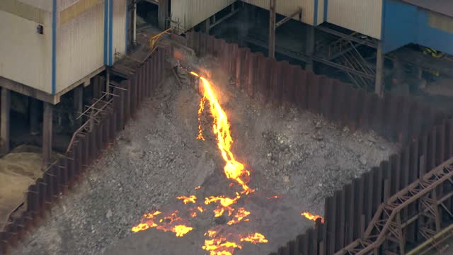 Aerial shots of the Port Talbot steelworks including shots of molten slag or spoil pouring out onto a heap next to one of the buildings at the...