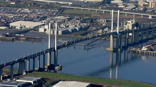 vídeos y material grabado en eventos de stock de aerial shots of the qeii bridge at the dartford crossing over the thames river and the surrounding industrial sites with container ships anchored at... - rodear