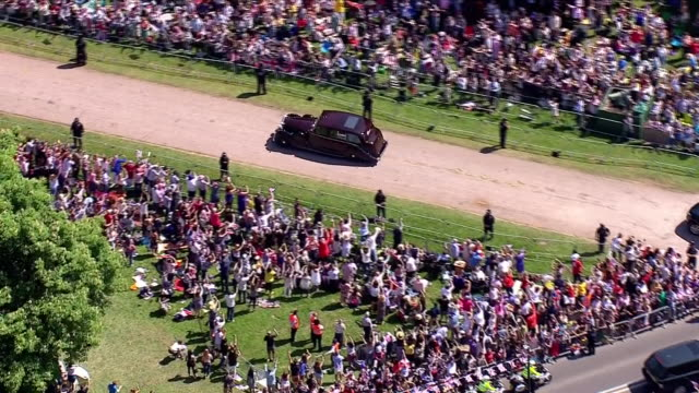 vídeos de stock, filmes e b-roll de aerial shots of the rolls royce vehicle carrying meghan markle and her mother doria ragland driving along the long walk past thousands of crowds as... - rolls royce