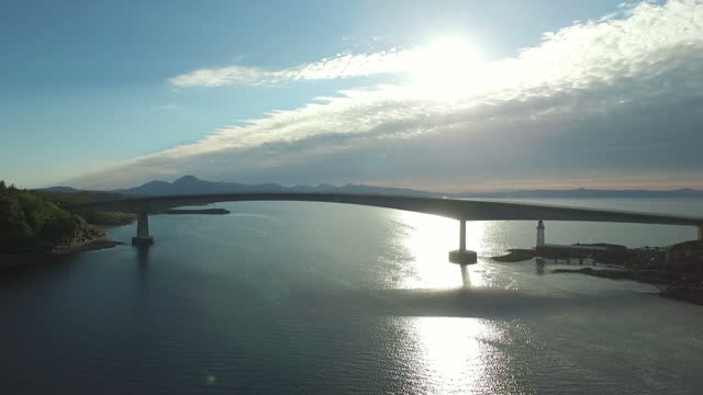 Aerial shots of the Skye Bridge over Loch Alsh connecting the Isle of Skye to the island of Eilean Ban with the sun sparkling off the water of Loch...