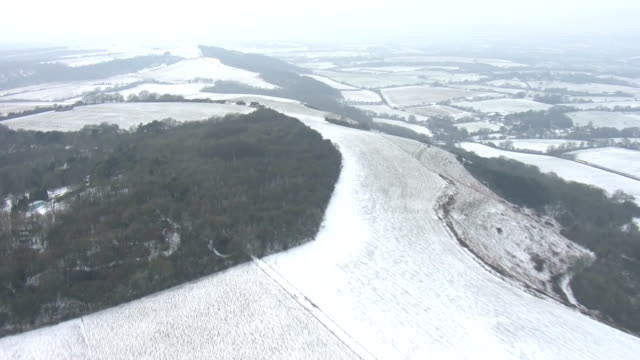 vídeos de stock e filmes b-roll de aerial shots of the snow covered landscape near southampton including views of the word 'southampton' spelled out by tracks made in the snow in a... - southampton inglaterra