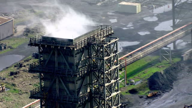Aerial shots of the steelworks at Port Talbot with a train wagon full of redhot material being towed to a tower and clouds of steam rising as the...
