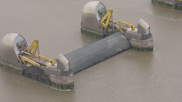aerial shots of the thames barrier on the river thames with some flood gates in the closed position many homes and businesses affected by flooding on... - river thames stock videos & royalty-free footage