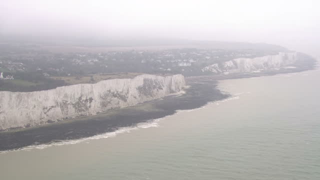 Aerial shots of the white cliffs of Dover in grey foggy weather mist clouds over the skyline on March 29 2017 in Dover England