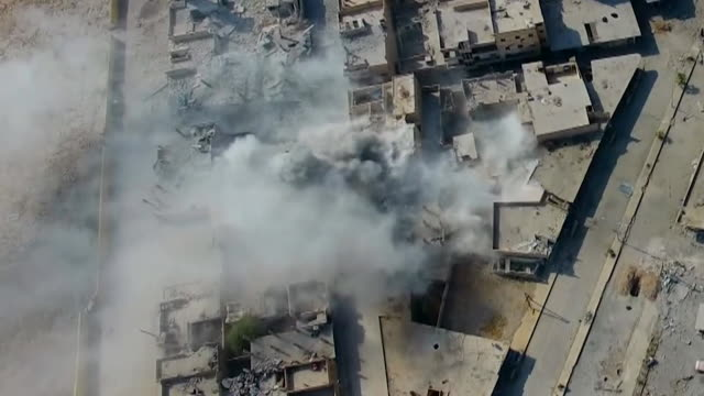 vidéos et rushes de aerial shots of western coalition air strikes on the city of raqqa, syria, 2017. - bombardement
