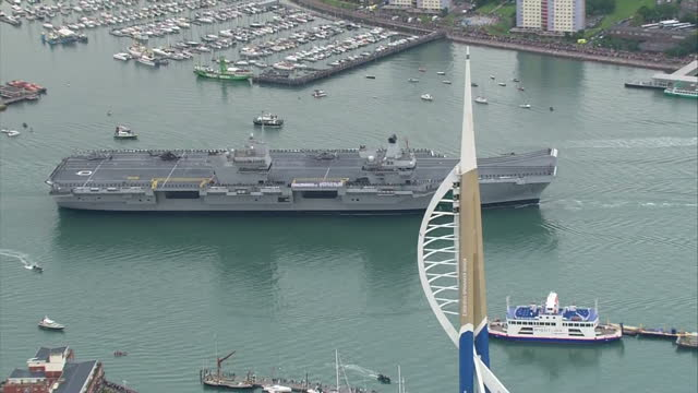 Aerial shots over Portsmouth Royal Navy's new Flagship aircraft carrier HMS Queen Elizabeth sailing into port flanked by a flotilla of ships sailors...