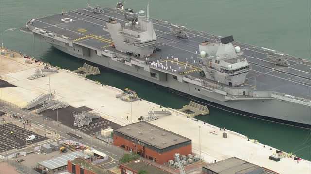 aerial shots over portsmouth royal navy's new flagship aircraft carrier hms queen elizabeth sailing into port flanked by a flotilla of ships sailors... - british military stock videos & royalty-free footage