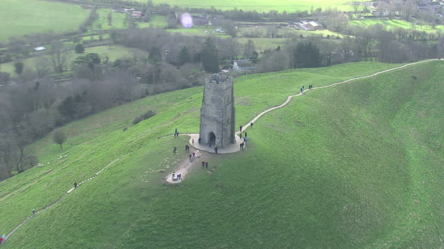 aerial shots st michael's tower on top of glastonbury tor with tourists walking around. on in somerset, united kingdom. - glastonbury tor stock videos & royalty-free footage