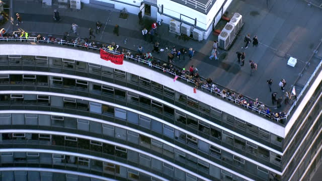 Aerial shots students protesting on the roof of Millbank Tower with a section throwing a fire extinguisher off the edge to the police crowds below...