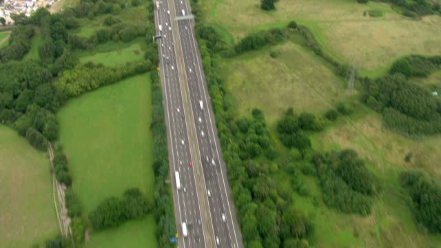 Aerial shots sweeping over the dual fourlane M25 motorway following the M3 from St Annes other lakes by Thorpe Park Green in Chertsey eastbound to...
