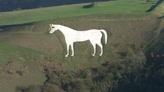 stockvideo's en b-roll-footage met aerial shots westbury white horse or bratton white horse on hillside on clear sunny day on in somerset united kingdom - wiltshire